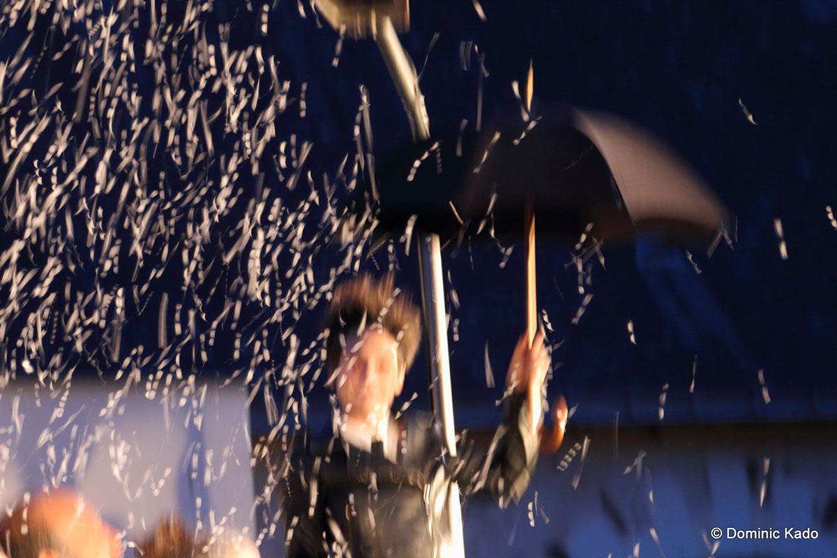 photo-floue-comédienne-avec-un-parapluie-confettis